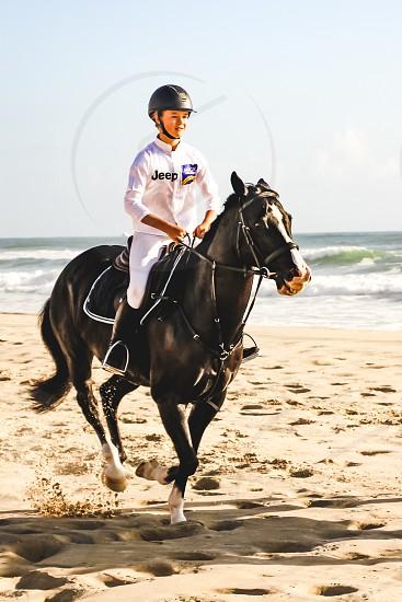 young girl horseback riding at the beach equestrian gallop photo