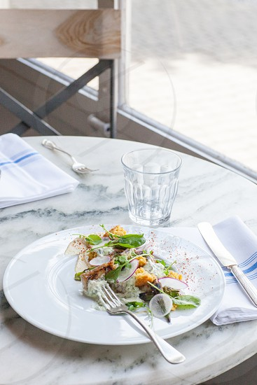 salad on ceramic plate with fork on top and clear drinking glass beside the plate during daytime photo