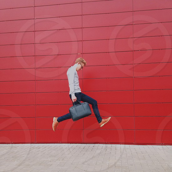 man holding grey suitcase galloping by the red wall photo