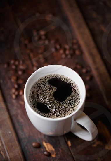 Fresh poured coffee with beans out of focus on a rustic wooden surface photo