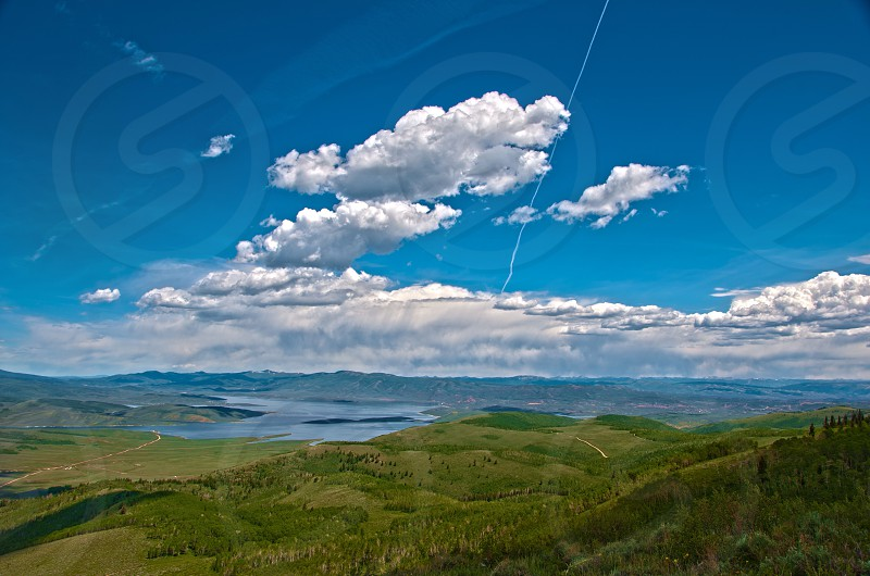 white cumulus clouds above green mountain photo