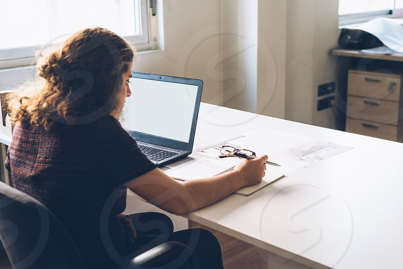Millennial female architect working with laptop at her desk photo