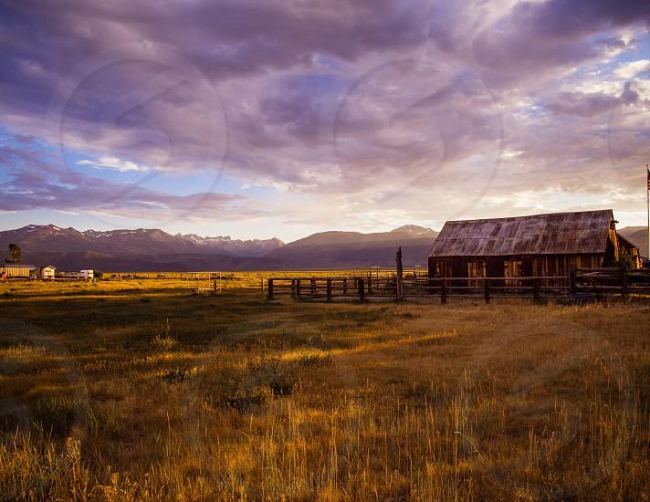 Sunset landscape looking across golden fields toward distant mountains. photo