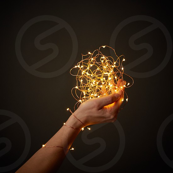 Yellow bright Christmas lights decorate the hand of a girl on a dark background with space for text. photo