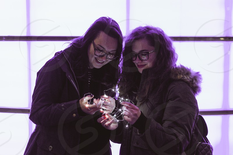 Two girls standing in front of a light wall holding fairy lights. photo