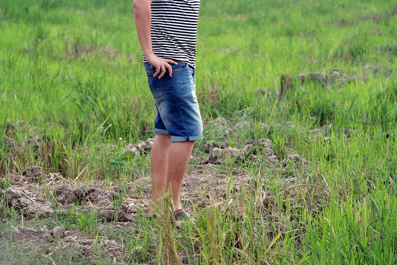 person wearing black and white stripe shirt and blue denim capri shorts standing at green grass during day time photo