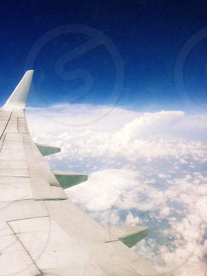 passenger wing plane on over white clouds under blue sky during daytime photo