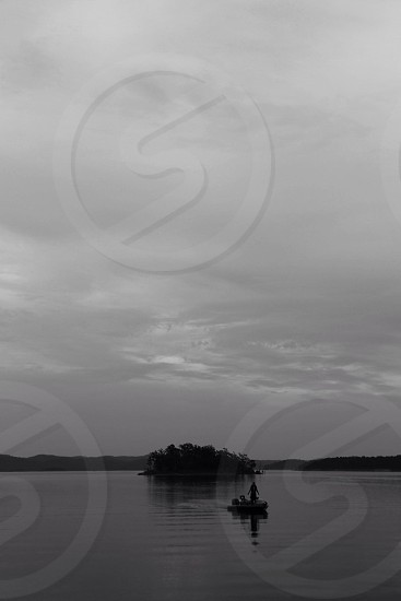 row boat on lake under cirrostratus clouds photo
