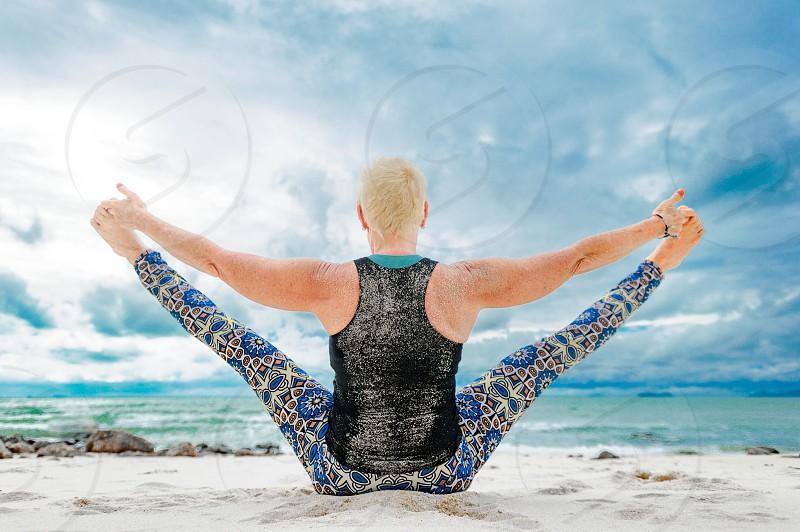 Beautiful mature aged woman doing yoga on a desert tropical beach. photo