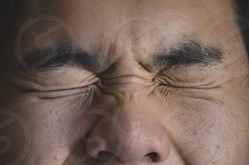 Closeup face wincing expression wrinkles man photo