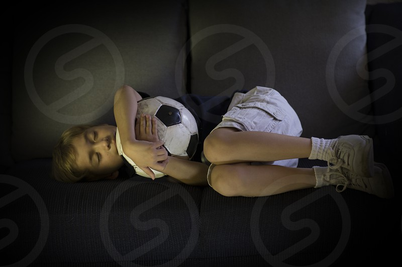 smiling boy with soccer ball watching camera enjoying football game and also dreaming about soccer photo