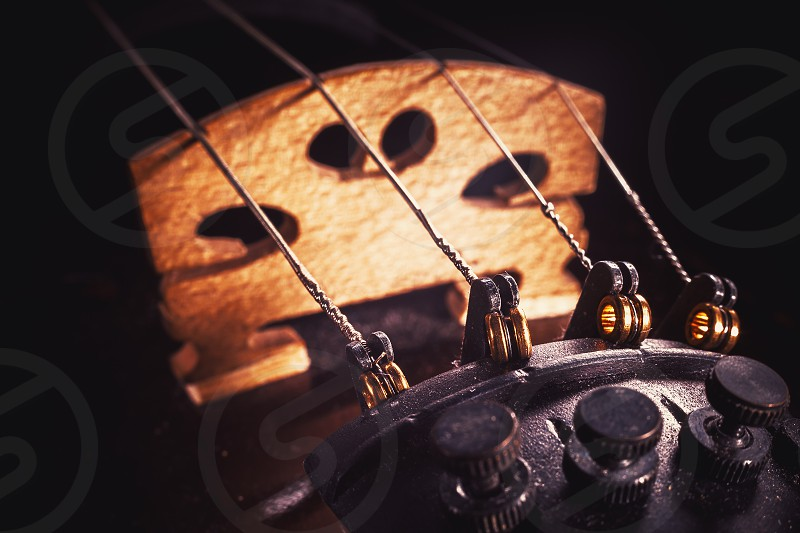 Closeup view of an old violin details of strings fine tuners and bridge.  photo