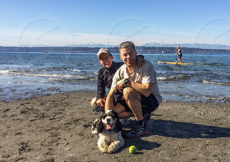 Couple at the beach with spaniel photo