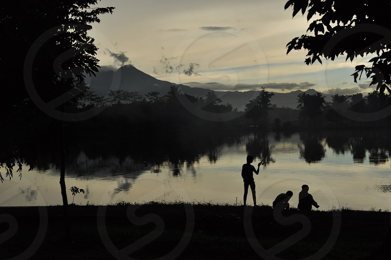 three people near body of water painting photo