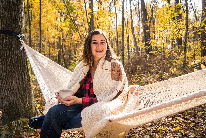 woman in red and black plaid sports shirt on white hammock during daytime photo