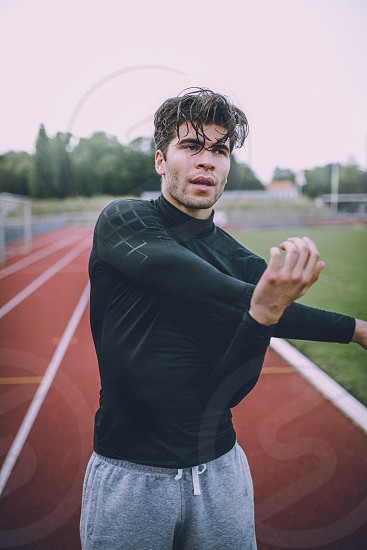 Young sports man is doing intense and hard workout at running track photo