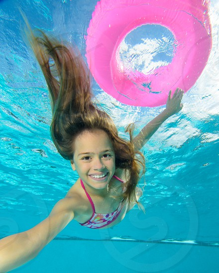 A young girl swimming underwater in the pool. photo