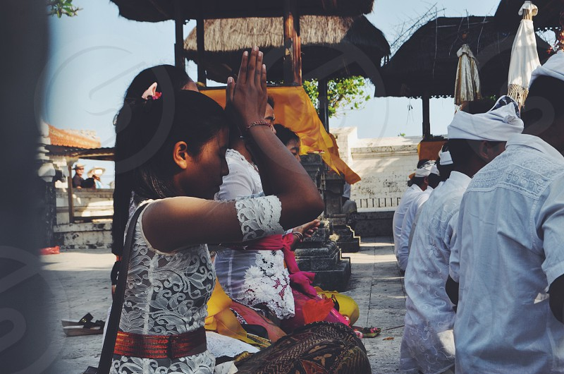 Bali Indonesia Uluwatu temple summer religion spiritual girl young family preyers Hinduism balinese religion exploring adventure hands reflection travel live authentic photo
