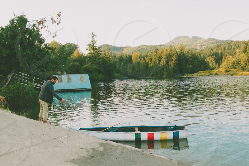 A young man getting his canoe ready for a paddle on the lake.  photo