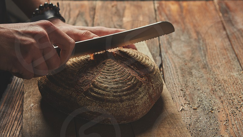 Hands of a man cutting fresh rye bread on a wooden background photo