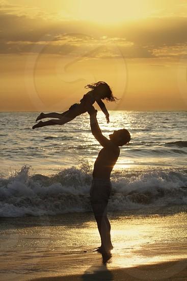 man throwing girl child in air at beachh photo