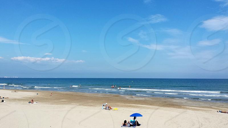 person under blue parasol near beach during daytime photo