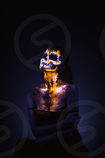 Girl's Face painted in fluorescent UV colors and looks like Neon Glowing Skull photo