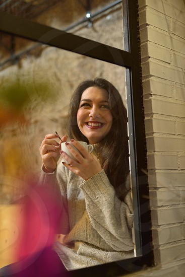Young woman having a coffee photographed through the window photo