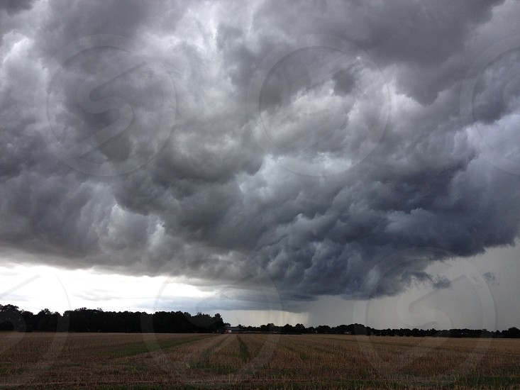 Field with storm clouds photo