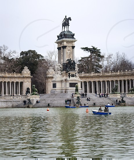 Madrid Spain February 2010: Equestrian monument to Alfonso XII with the lake and the tourists on the boats inside the Parque del Buen Retiro photo