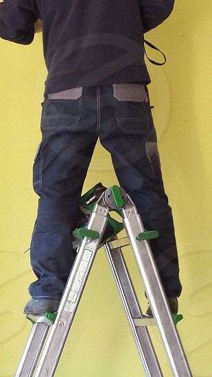 man wearing black denim jeans standing on grey metal step ladder photo
