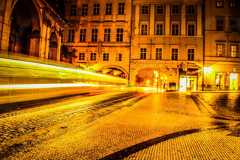 Light trails of a tram & car passing by at the entrance of the Charles Bridge Prague Czech Republic. photo