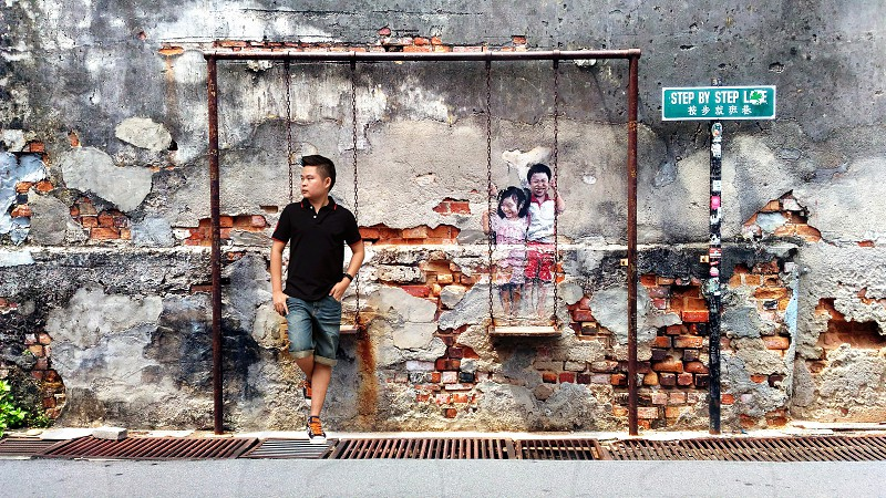 man leaning on wall with swing chair 3d painting beside road during daytime photo