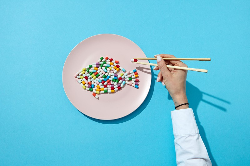 Different pills and supplements as a fish on a white plate chopsticks in woman's hands with shadows on a blue. Suppressants for dieting concept. Top view. photo
