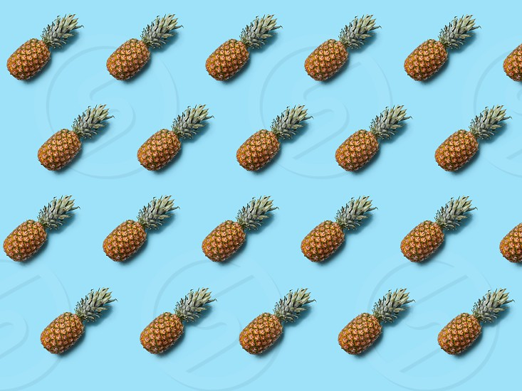 Exotic fruit pineapple with leaves on a blue background as layout for your ideas. Flat lay photo