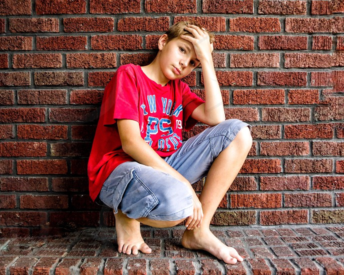 boy in red shirt with blue cargo shorts squatting on red brick wall and floor photo