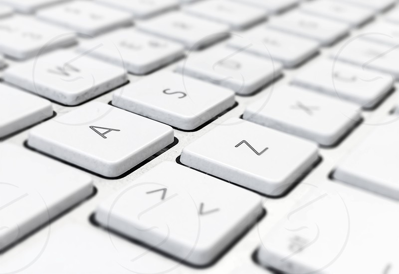 Close-up detail of a computer keyboard with white keys and a gray background. Letters and symbols on the keys. Technology and communication via the internet photo