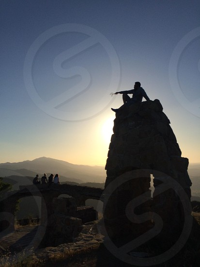 man sitting top of pilled stone photograph photo