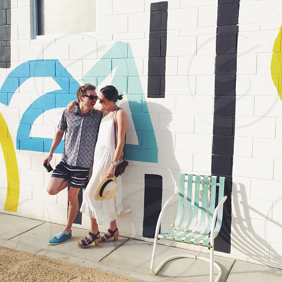man and woman leaning on wall photo