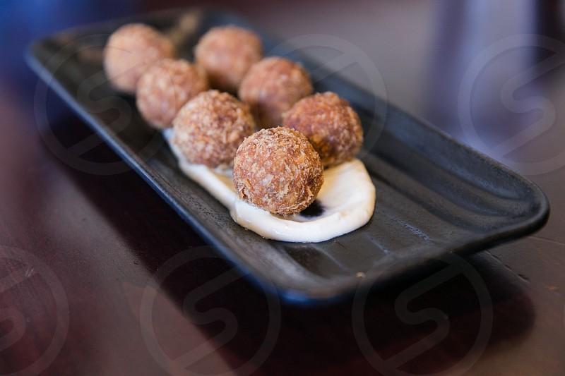 7 brown truffles on black rectangular clay tray photo