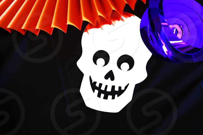 Halloween paper craft design with white skull and orange fan on black background photo