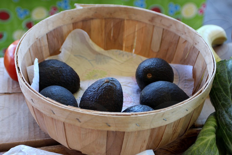 Avocados in wooden basket at farmers market photo