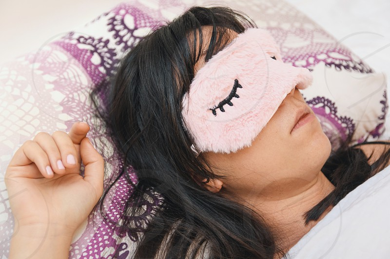 Attractive young woman asleep in her bed. Woman wearing an eye mask. Pillow linen bright lifestyle at home nap sleepyhead. photo
