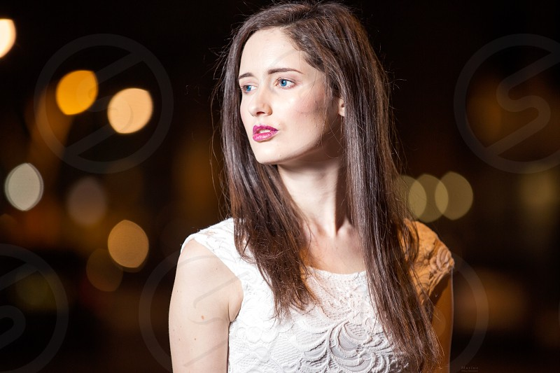 Young woman with dark hair and blue eyes looks dreamy aside in the night.In the background you see some lights of the night! photo