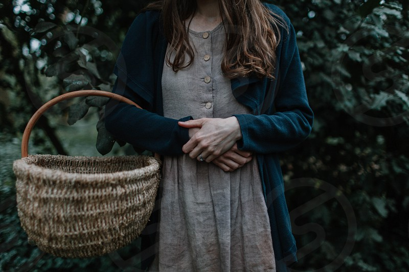 Natural dye artist collects nettles in the woods with her basket. photo
