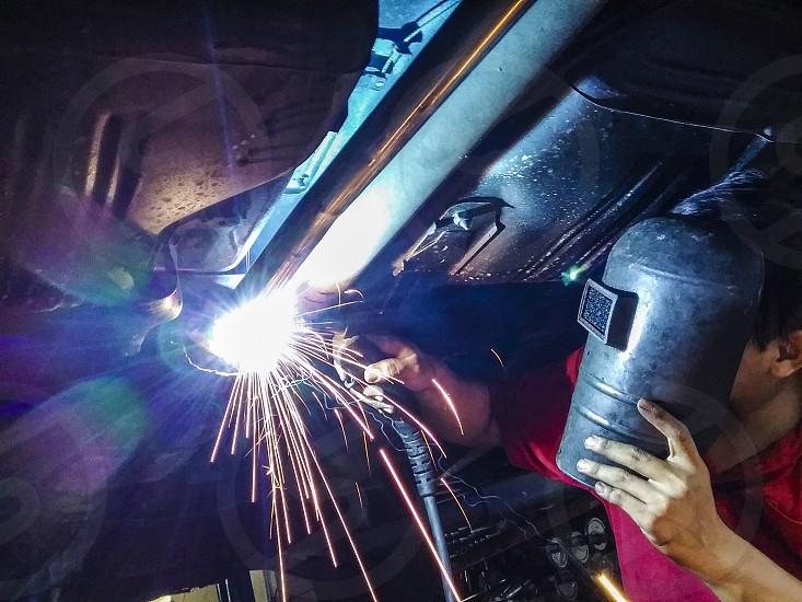 Blue collar worker welding car undercarriage photo