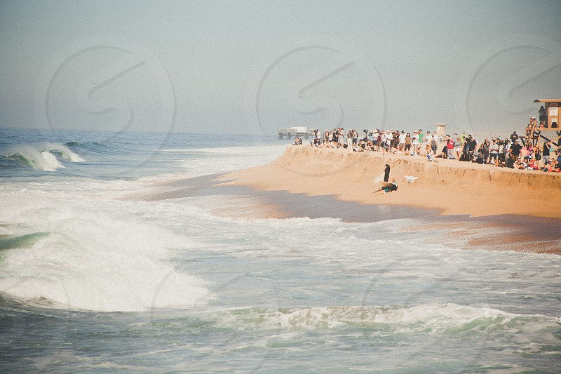 water waves hitting shore with people standing on side photo