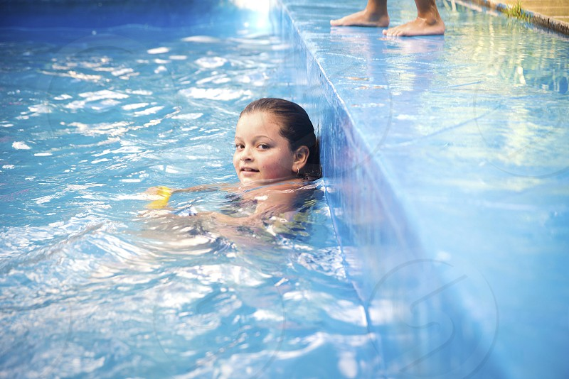 girl relaxing inside a water moving swimming pool looking at camera feet of other person in the background photo