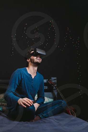 Young man wearing virtual reality glasses and sitting on sofa in a room photo