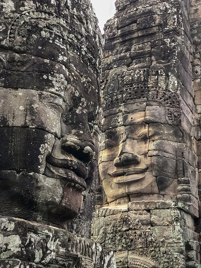 Outdoor day colour vertical portrait Angkor Thom Angkor Wat National Park Siem Reap Cambodia Asia Asian east eastern ancient holy spiritual Khmer dynasty monument face faces sky blue white clouds summer travel tourism tourist wanderlust stone carved ornate elaborate figure figures temple photo